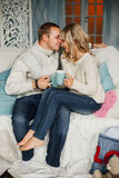 In love young couple on a sofa, laughing and Stock Photo