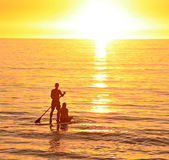 Love. A young couple together on a paddle board watching the sunset Royalty Free Stock Images