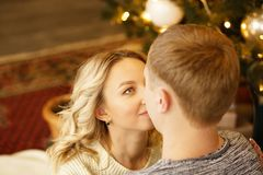 Love young happy family, the couple kissing, sitting near the Christmas tree in the room. Happy New Year and Christmas. New year`s interior royalty free stock photography