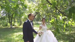 In love a young wedding couple is walking in the park. A husband with his wife in white bride wears a walk in nature. 1 stock video