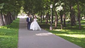 In love a young wedding couple is walking in the park. A husband with his wife in white bride wears a walk in nature stock footage
