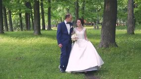 In love a young wedding couple is walking in the park. A husband with his wife in white bride wears a walk in nature. 1 stock video footage