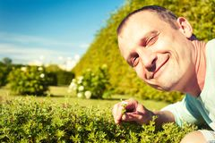 Love your planet-save the nature! Happy man with flower. Love your planet-save the nature! Portrait of happy cheerful man face holding small flower in green Stock Photography