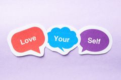 Love your self. Concept paper bubbles against purple background Stock Images