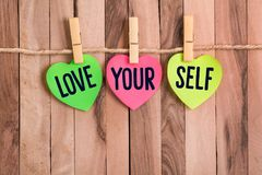 Love your self heart shaped note. Love your self text in color heart shaped note with clothespin and rope on wooden background royalty free stock photography