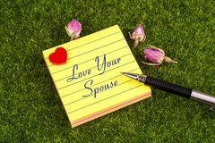 Love your spouse note. Love your spouse in sticky note with heart , pen and dried rose on grass Stock Photo
