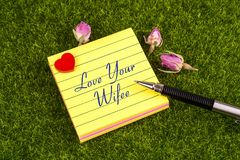 Love your wife note. Love your wife in sticky note with heart , pen and dried rose on grass Royalty Free Stock Photo