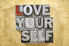 Love yourself phrase. Made from metallic letterpress type on grunge cardboard background Royalty Free Stock Photo