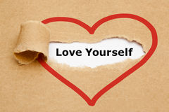 Love Yourself Torn Paper. The text Love Yourself appearing behind torn brown paper Royalty Free Stock Photography