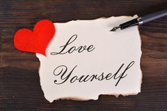 LOVE YOURSELF. Word in burned paper with heart and pen on wood royalty free stock photos