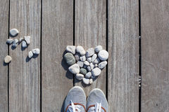 Love, Zen, Balance, Life Concept. Shape of heart made with stones with shoes on the wooden planks of pier background. Love, Zen, Balance, Life Concept stock images