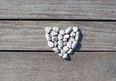Love, Zen, Balance, Life Concept. Shape of heart made with stones on the wooden planks of pier background. Love, Zen, Balance, Life Concept stock photos