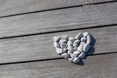 Love, Zen, Balance, Life Concept. Shape of heart made with stones on the wooden planks of pier background. Love, Zen, Balance, Life Concept royalty free stock image