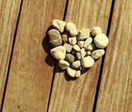 Love, Zen, Balance, Life Concept. Shape of heart made with stones on the wooden planks of pier background. Love, Zen, Balance, Life Concept. Toned in warm color royalty free stock photo