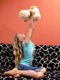 Loved dog. Blond young girl on sofa holds her beloved toy - plush dog Royalty Free Stock Photography