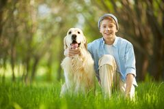 Loved friend. Portrait of cute lad embracing his white labrador Stock Photos