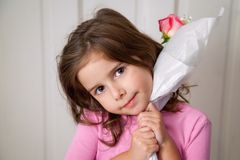 Loved Girl With Rose. A young girl with big, brown eyes, holds a single, pink rose close to her chin in somewhat of a hug.  She looks pleased with her rose with Stock Image