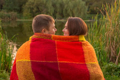 Loved pair, middle-aged man and women wrapped in plaid. Royalty Free Stock Image