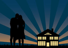 In Loved Silhouettes. Young cople embraced dreaming to their house Royalty Free Stock Photo
