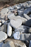 Loveing wooden heart on the rocks Stock Photos