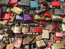 Lovelocks background. Lovelocks with signs and hearts engravings fastened to a bridge fencing, close-up full frame background image Stock Image