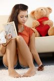 Lovelorn teenage girl at home. Lovelorn teenage girl sitting on floor at home, looking sad stock photography