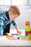 Lovely 3 year old lost in playing stock photography