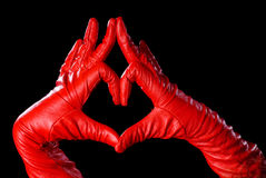 Lovely. Hands in red gloves on the black background showing love Stock Photo