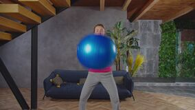 Sporty fit woman squatting with stability ball indoors