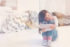 Lovely admirable child hugging her knees royalty free stock photography