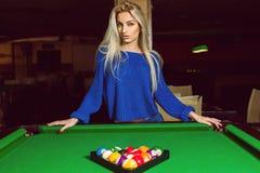 Lovely adult blonde posing near a billiard table with a pyramid Stock Photos