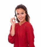 Lovely adult secretary speaking on headphones Royalty Free Stock Photography