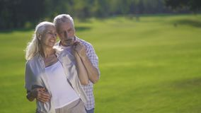 Lovely affectionate couple enjoying in countryside. Portrait of lovely affectionate senior couple enjoying time together in countryside. Beautiful mature husband stock footage
