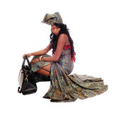 Lovely African American woman crouching. A beautiful African American woman crouching in an African long dress Stock Photography