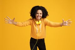 Lovely african american young woman with bright smile dressed in casual clothes and headphones ready for hugs over. Yellow background royalty free stock photo