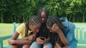 Lovely african teenage girls watching social media content online on phone