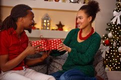 Lovely afro American couple exchanging presents on Christmas Royalty Free Stock Image