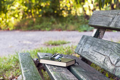 Lovely afternoon outdoors with sunglasses and book on a bench Royalty Free Stock Photos