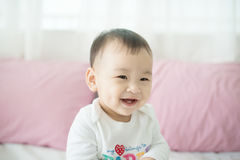 Lovely asian baby girl sitting on bed at her room. Stock Images
