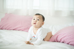 Lovely asian baby girl sitting on bed at her room. Royalty Free Stock Photos
