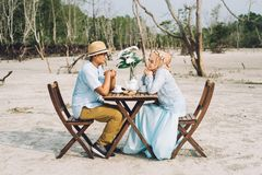 Lovely asian couple having a romantic moment of happiness outdoor with picnic table and chair Stock Image