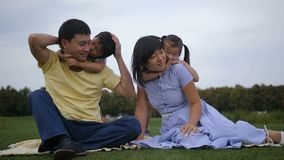 Lovely asian family with siblings relaxing at park stock footage