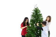 The lovely Asian family spending their precious time as a family. On a special day of christmas by decorating the hugh christmas tree. The white background with royalty free stock photography