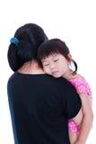 Lovely asian girl sleeping on mom's shoulder, over white backgro Royalty Free Stock Photo