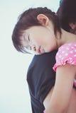 Lovely asian girl sleeping on mom's shoulder, on white backgroun Stock Image
