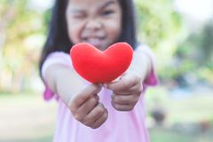 Lovely asian little child girl showing and holding red heart royalty free stock photography