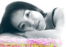 Lovely Asian model in black and white poses on superimposed bed of colorful tulips. A lovely Asian girl rests her head on her arms in a black and white pose royalty free stock photography