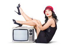 Lovely asian pinup girl posing on vintage tv set Royalty Free Stock Photos