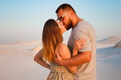 Lovely attractive couple kissing on the white sand beach or in the desert or in the sand dunes, happy couple embracing at the beac royalty free stock photos
