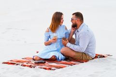 Lovely attractive couple sitting together on the white sand beach, couple with wine or champagne during romantic dinner, young cou Royalty Free Stock Photos